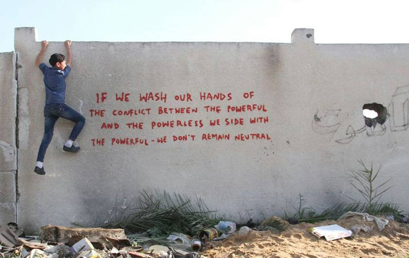 [IMG ~ Banksy in Gaza: graffiti       on wall: 'If we wash our hands of the conflict between the       powerful and the powerless we side with the powerful -- we don't       remain neutral' ]